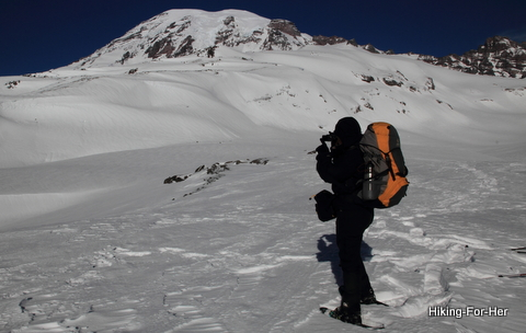 Female snowshoer wearing appropriate winter gear and a backpack, taking photos of Mount Rainier from a snowy ridge