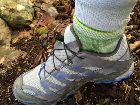 Gray and blue hiking shoe with green hiking sock
