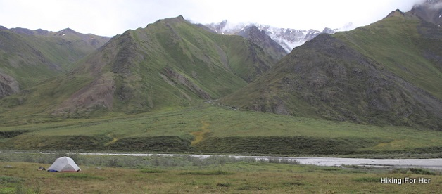 White backpacking tent with towering mountains and a river behind it in Alaska