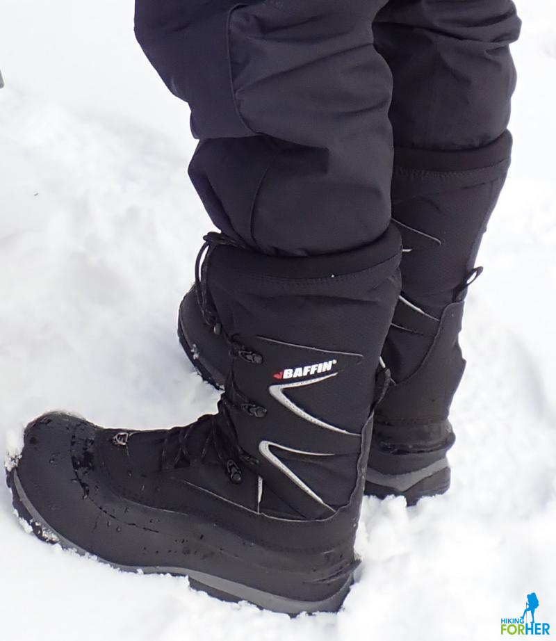 Legs and feet of a winter hiker in warm, waterproof boots and pants