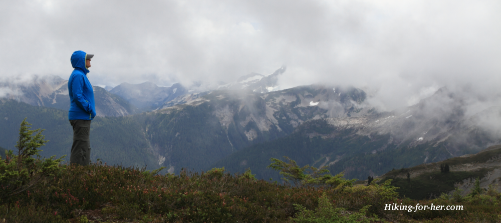 Female hiker in a blue jacket gazing at misty mountains