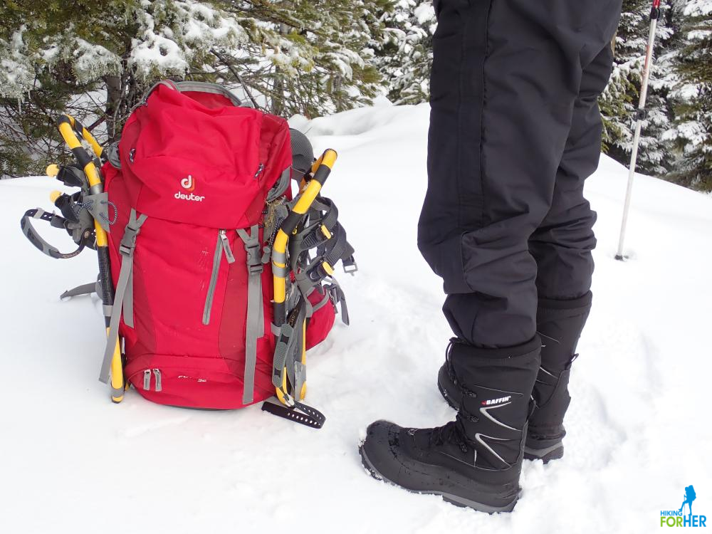 Red backpack with yellow snowshoes strapped to the sides, next to a pair of black winter Baffin boots on a hiker's legs