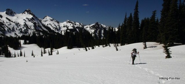 Female hiker using trekking poles as she crosses a snow field with snowy mountains behind her