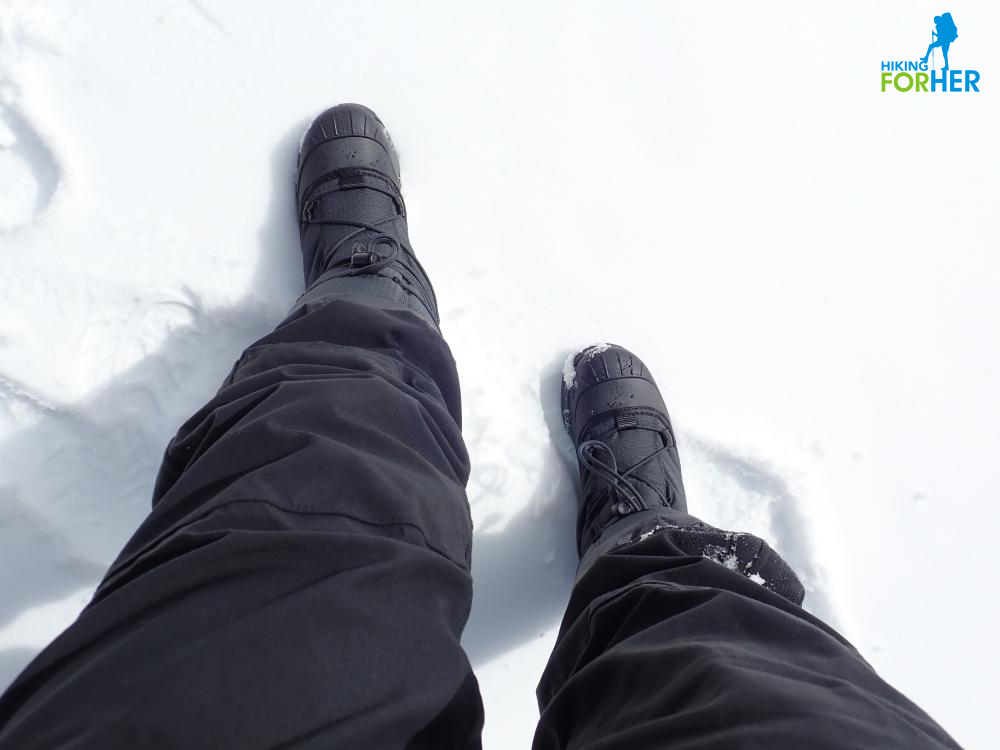 Black winter boots and snowpants in the snow