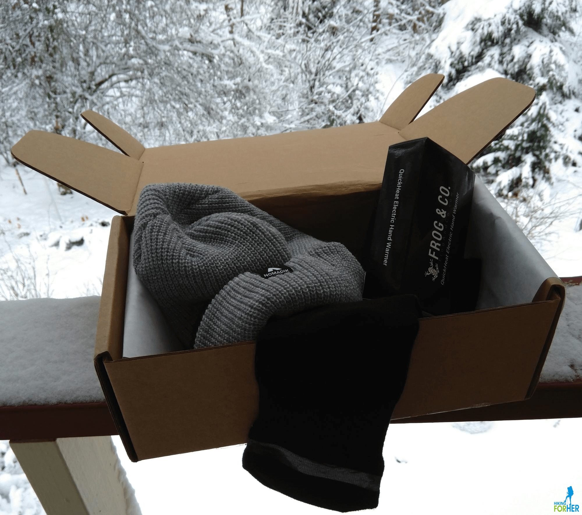 A gray hat, black socks and a small black box inside a brown cardboard box with a snowy background