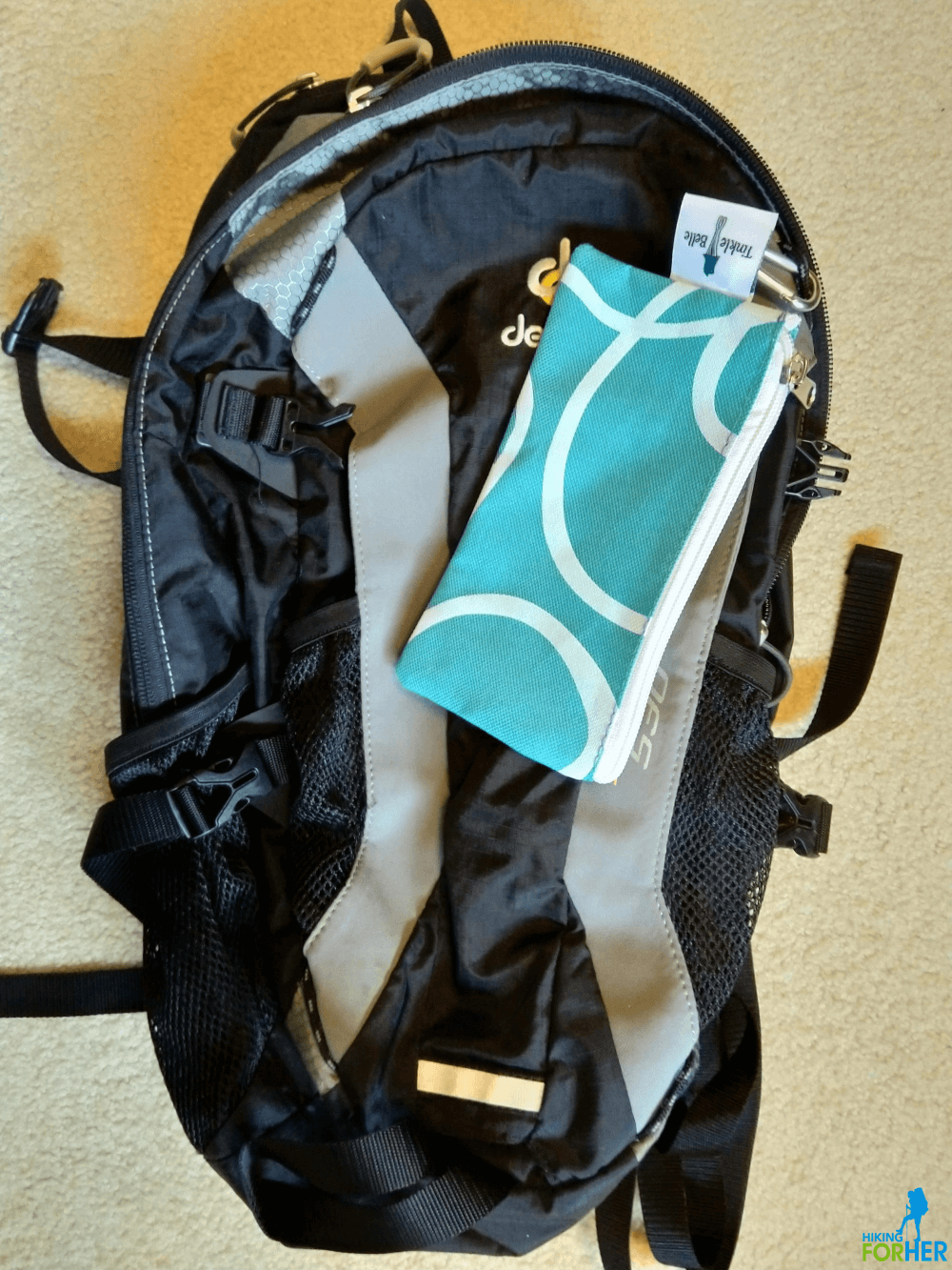 TinkleBelle carrying case clipped to hiking daypack with a small carabiner