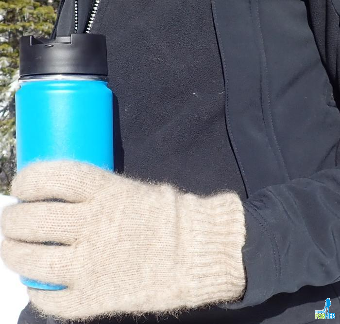Gloved hand holding bright blue insulated metal bottle during a hike