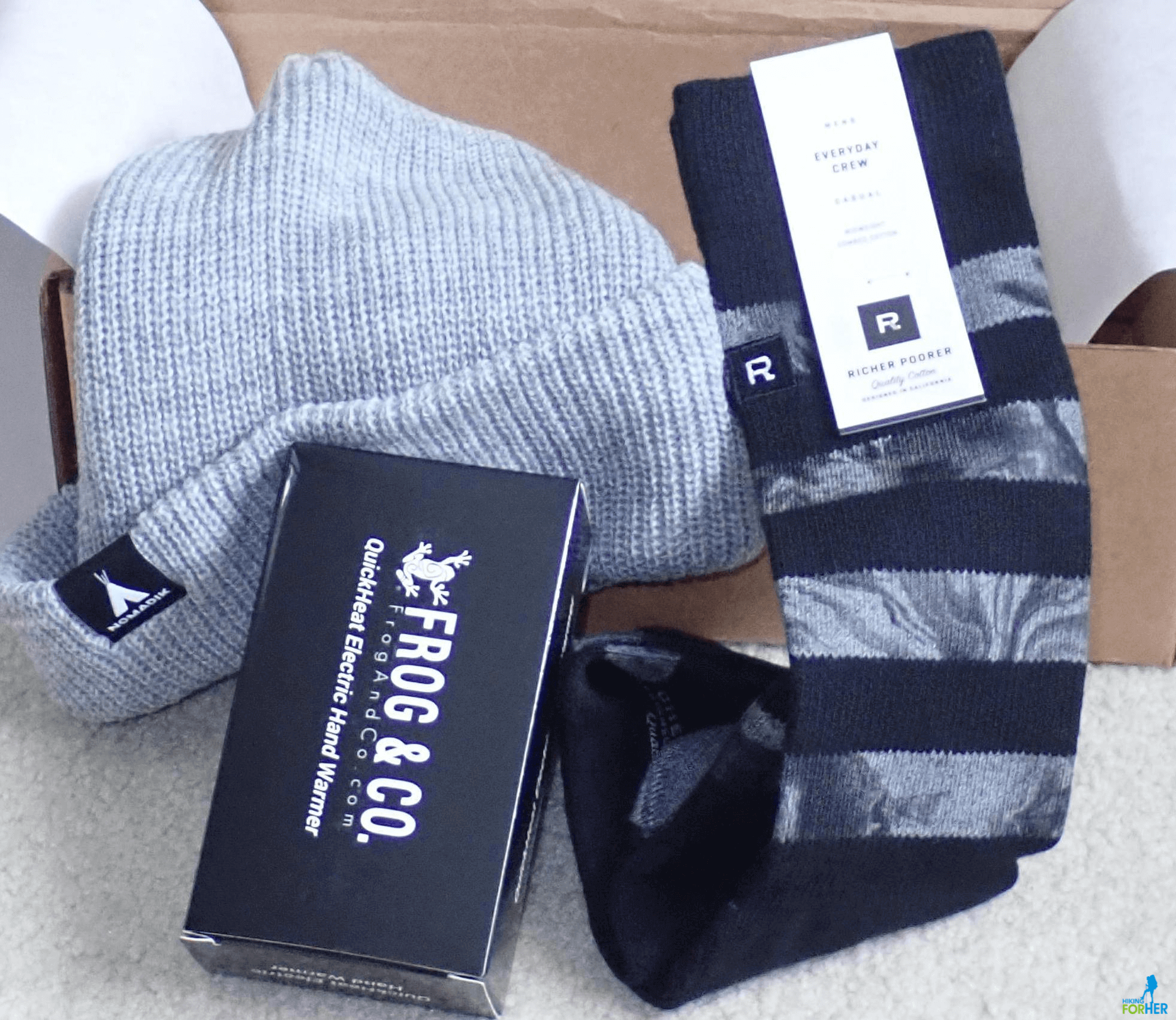 The Nomadik subscription box contents: gray hat, striped socks, hand warmer