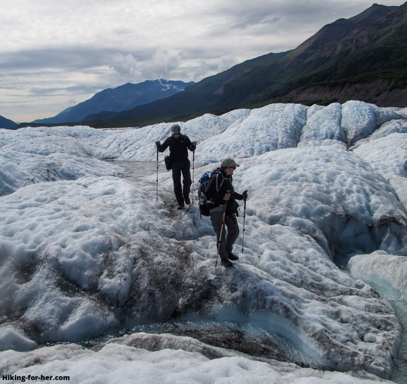 Two hikers exploring the surface of a glacier