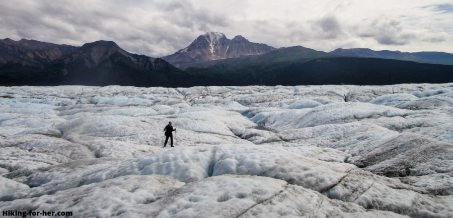 Hiker striding across surface of Nizina Glacier, Alaska