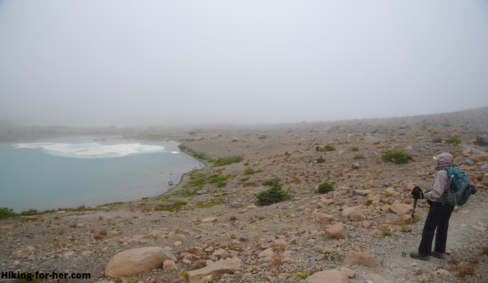 Female hiker in rain gear on a foggy trail near an alpine lake with small ice floe