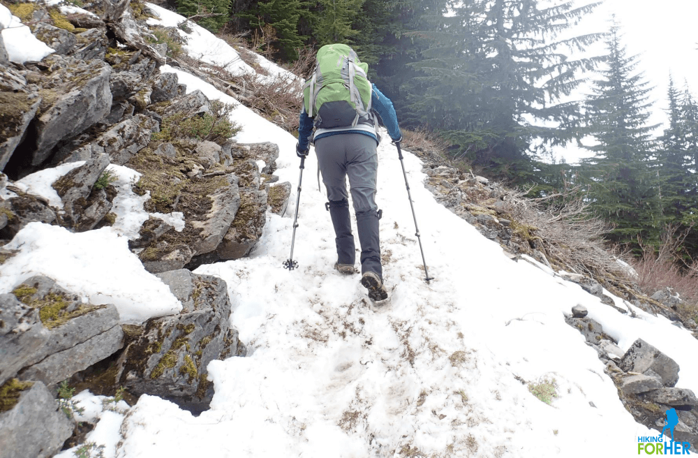Female hiker wearing green backpack using trekking poles to ascend steep snowy trail