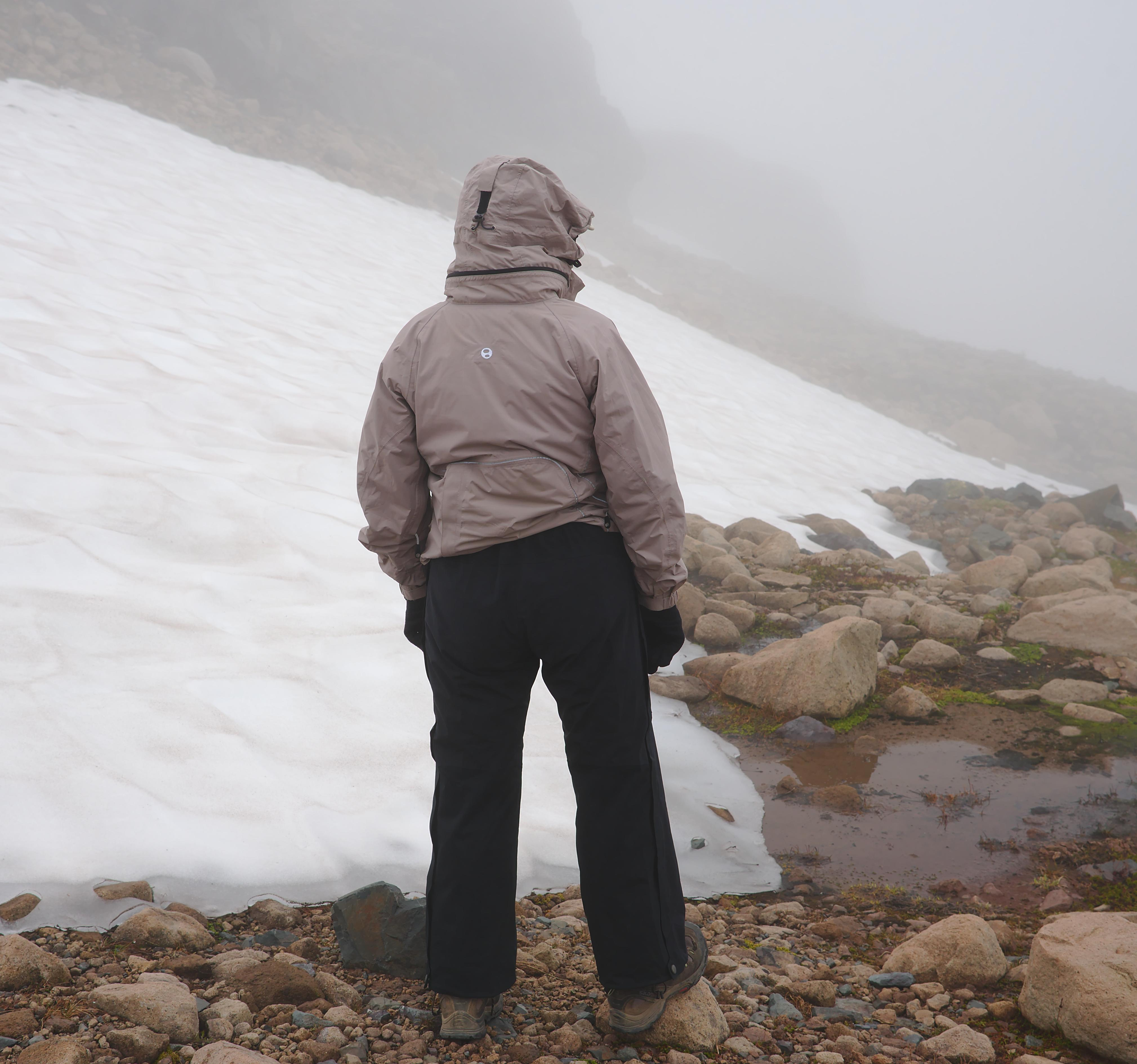 Female hiker wearing rain jacket and rain pants in fog on a mountain slope