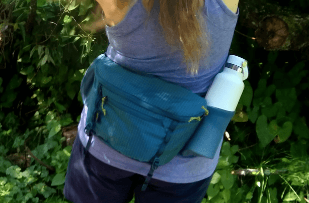 Female hiker in tank top and shorts wearing a ball cap and fanny pack