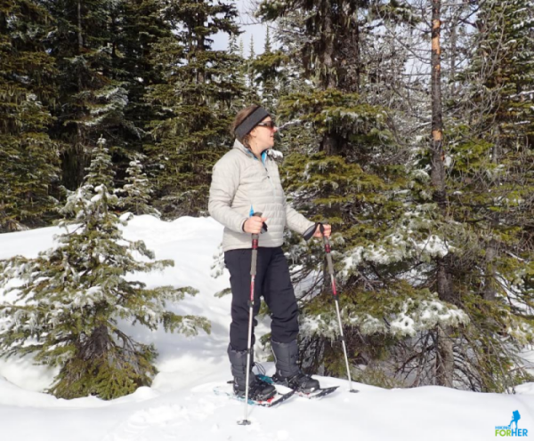 Female snowshoer with winter boots and trekking poles