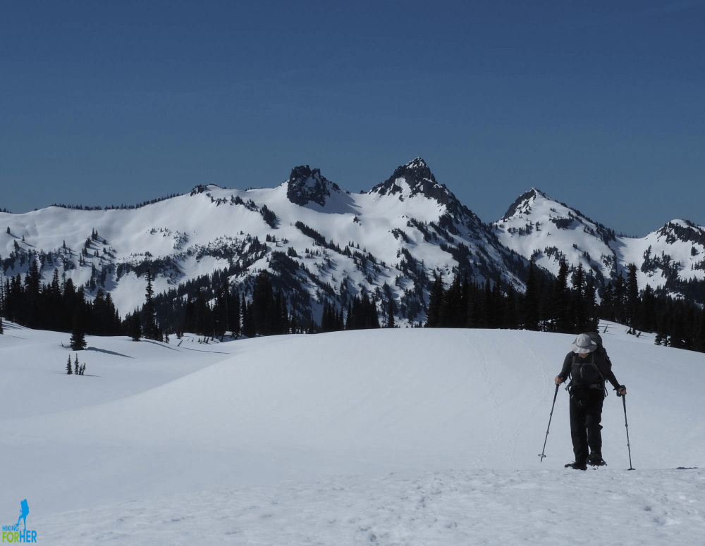 Female snowshoer with backpack and trekking poles, snow covered Tatoosh Range behind her