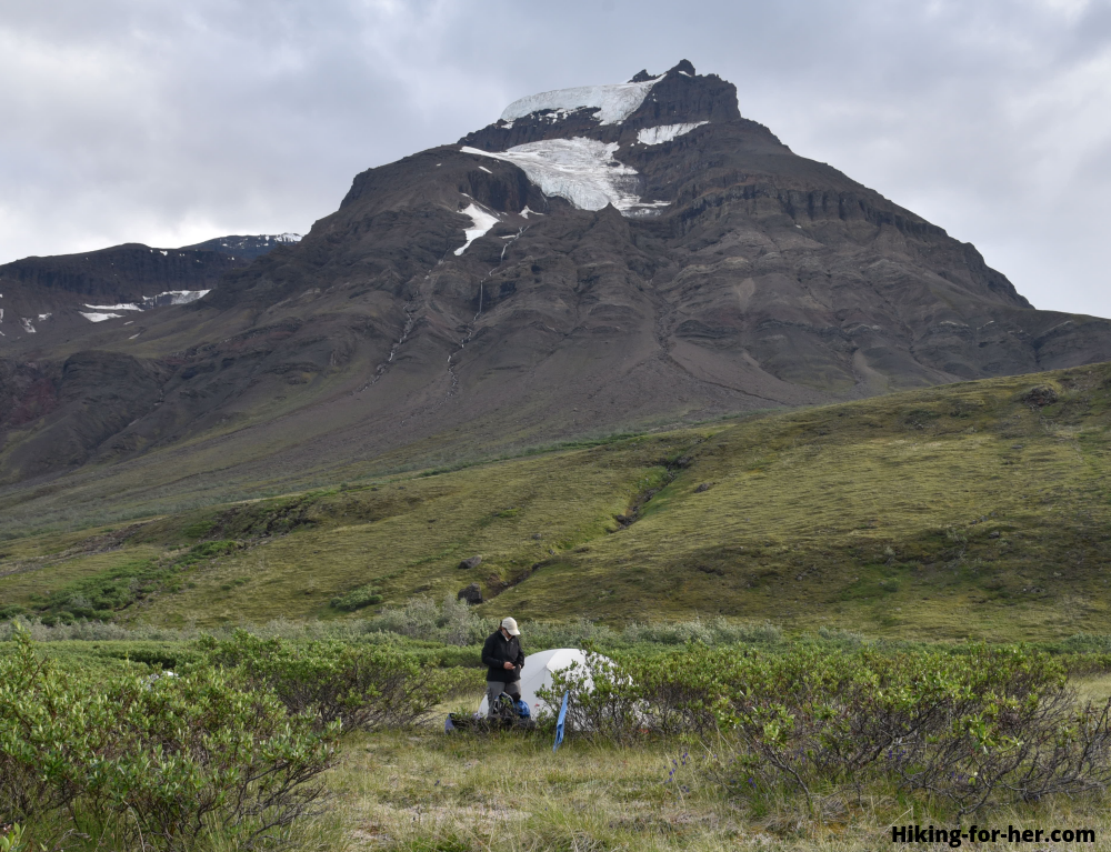 Female backpacker outside her tent with rugged mountains in background