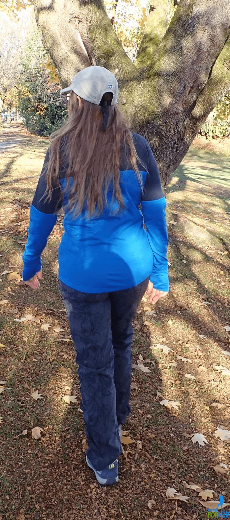 Female hiker walking toward towering tree