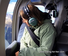 Female heli-hiker wearing ear protection inside a helicopter as she gazes out the window at the peaks below