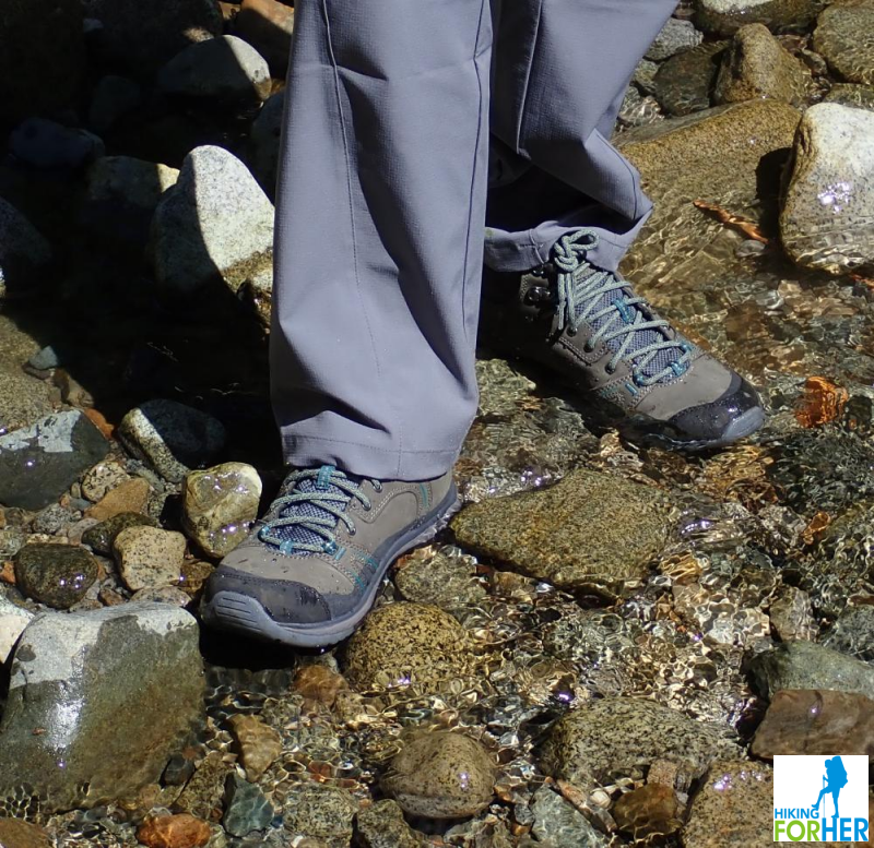 A hiker in waterproof hiking boots wading in a clear stream