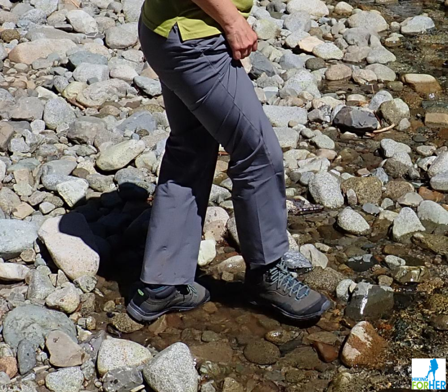 Female hiker walking on rocky river bank with boots in the water