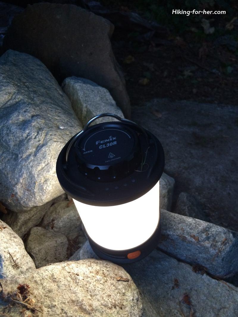 Glowing camping lantern perched on rocks