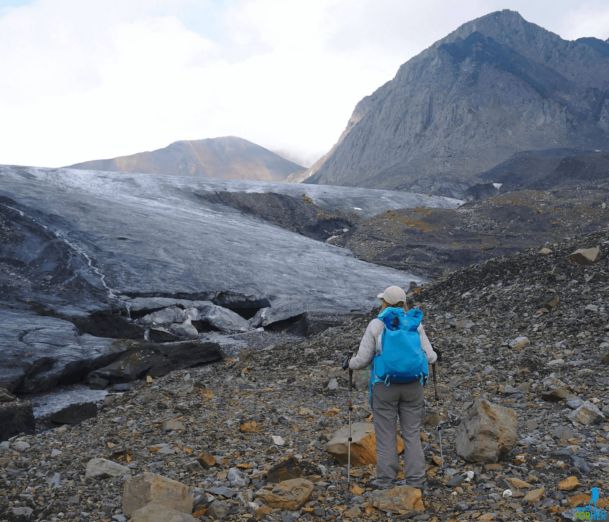Female hiker wearing blue backpack and carrying trekking poles on a hike along a glacier