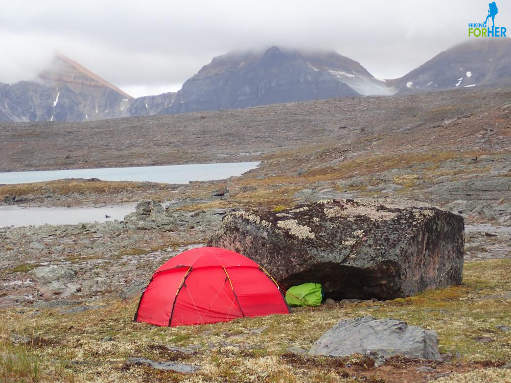 Red dome backpacking tent against a huge black boulder with alpine lake in background