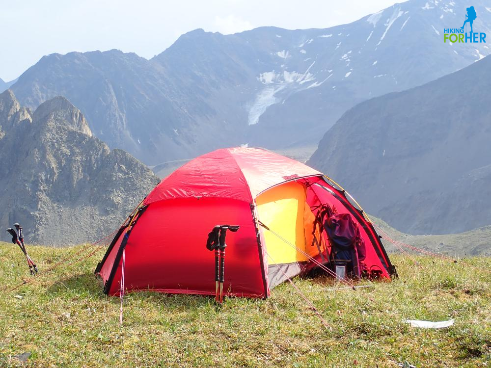 Red and yellow Hilleberg tent, one rain flap open to reveal backpack and hiking poles, in a mountain setting