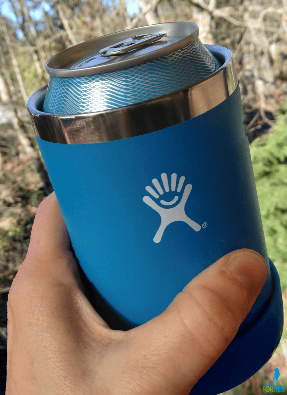 Hand holding a blue Hydroflask Cooler Cup, which in turn is holding a beverage can