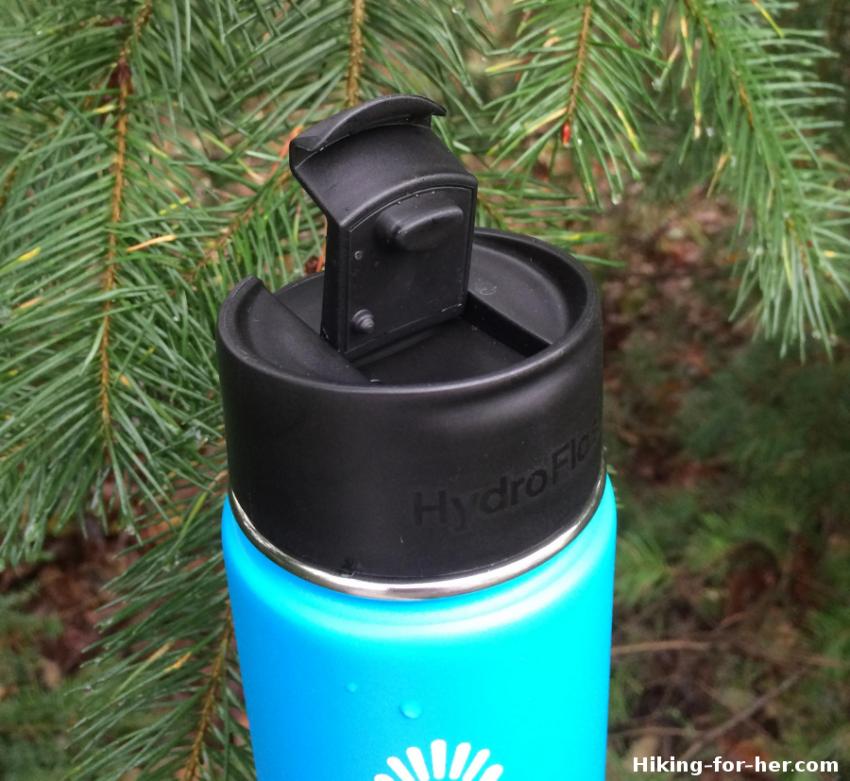 Blue wide mouth Hydroflask bottle beneath a fir tree