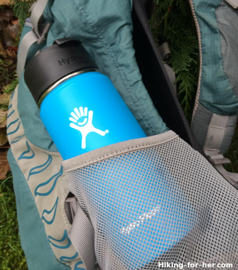 Blue wide mouth Hydroflask in the mesh pocket of a hiking backpack