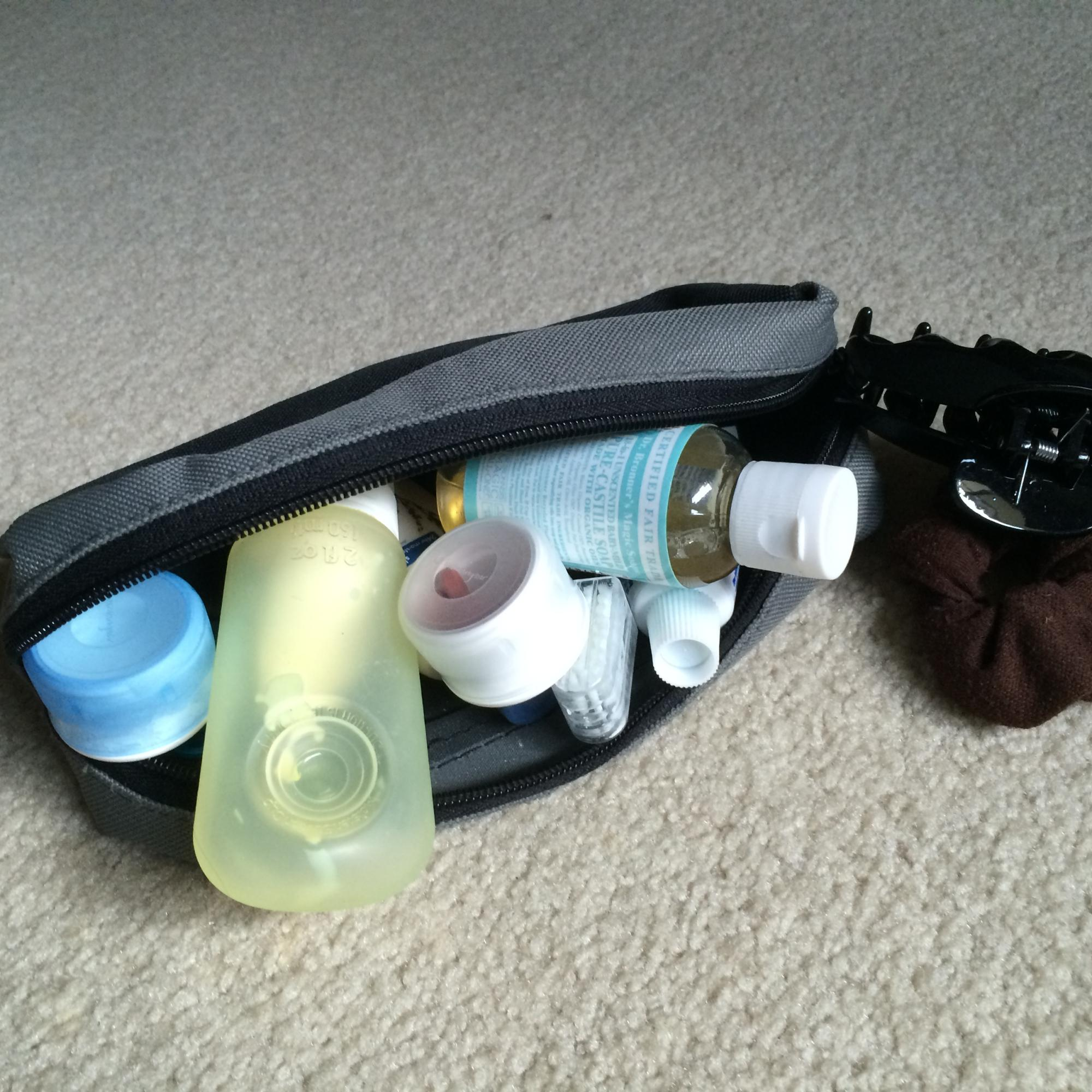 Woman's backpacking hygiene kit containing biodegradable soap, toothbrush, toothpaste, and face cream