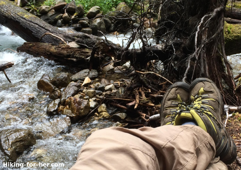 Hiker's legs and feet with hiking boots propped up against a log, beside a running creek