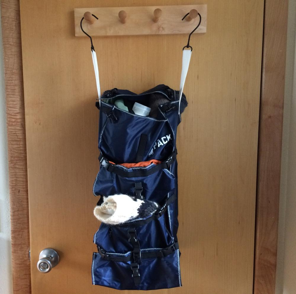 Backpack organizer hanging on back of door with white straps and metal hooks