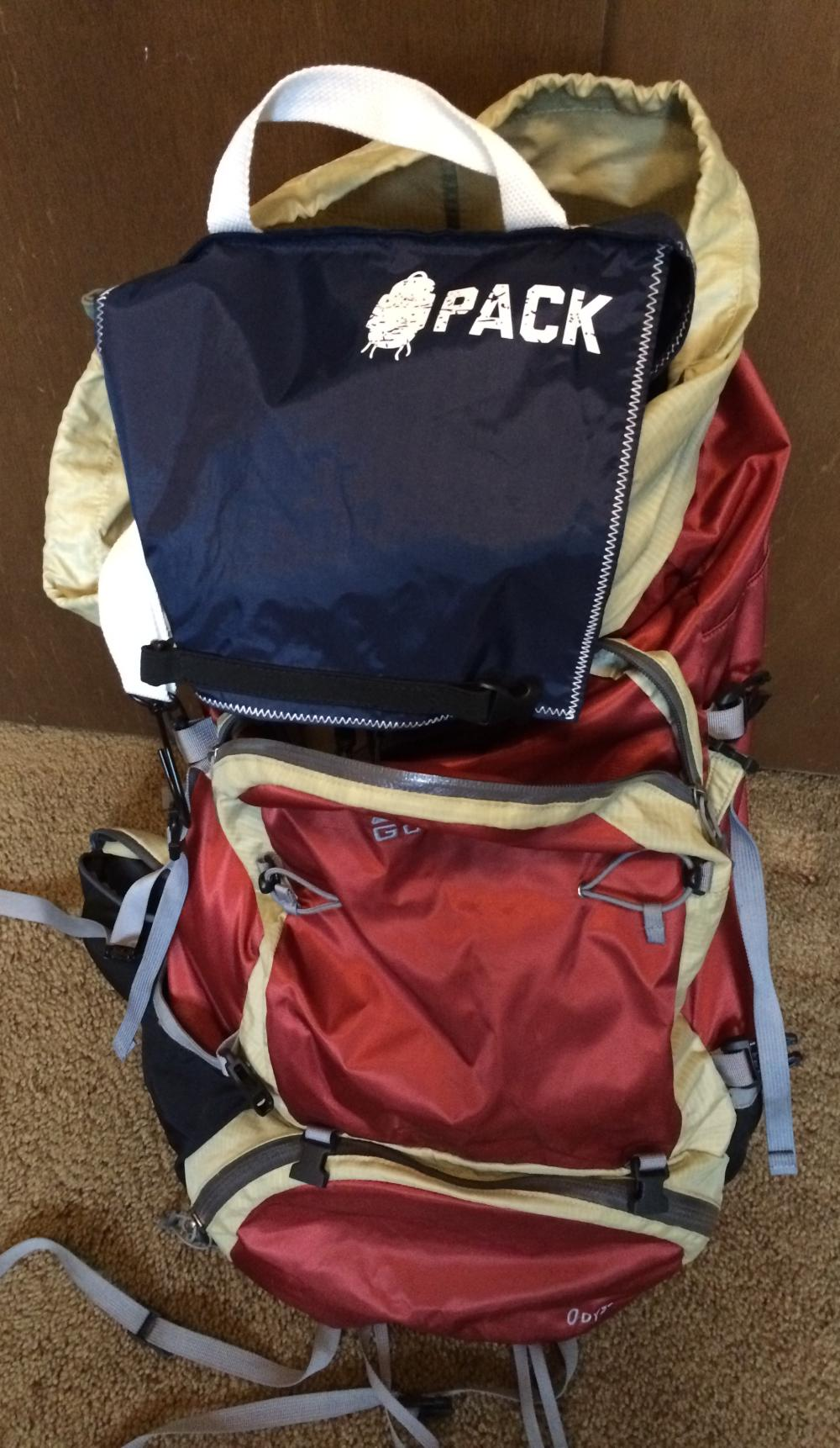 Packing a backpack might require internal organizers, like this navy blue one sitting on an orange and yellow backpack