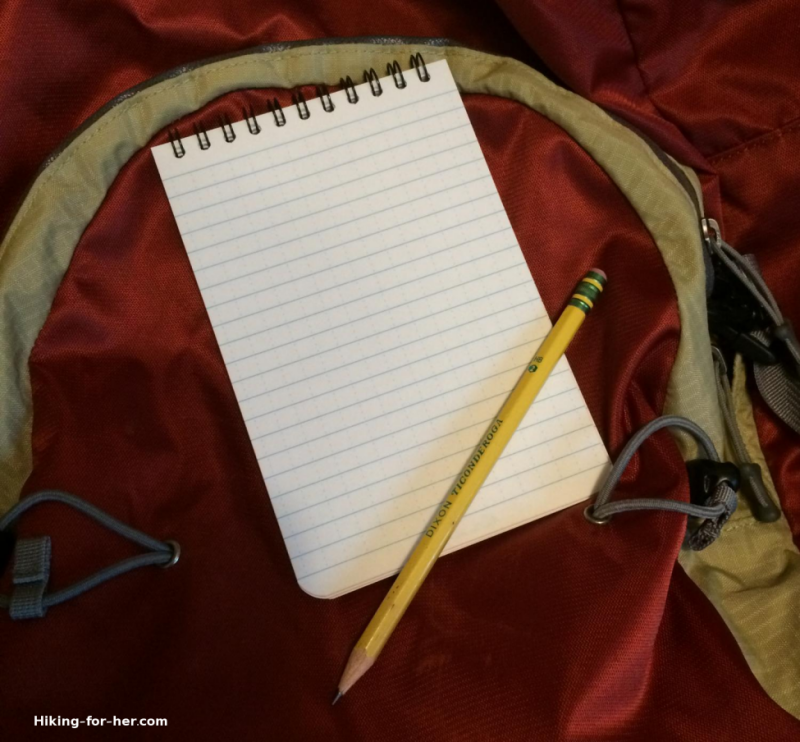Trail journal and pencil resting on a backpack