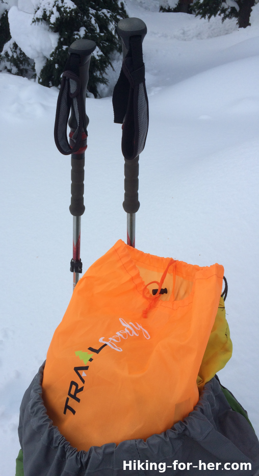 Hiking poles and orange lunch sack on snowy trail