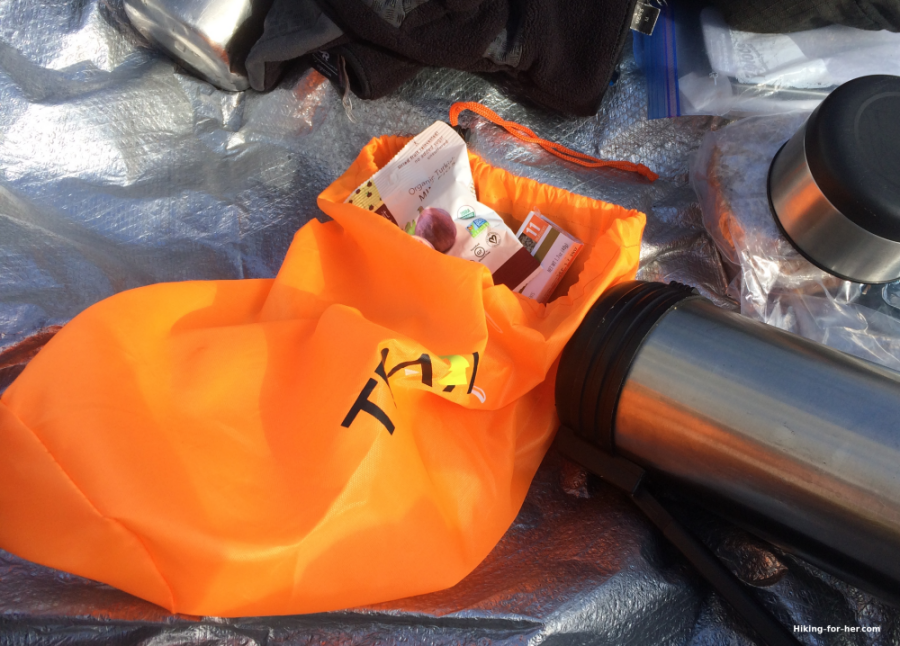Orange lunch sack and metal thermos on a tarp thrown over snow