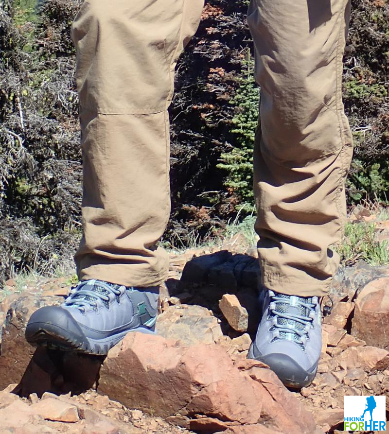 Female hiker's legs and feet in tan hiking pants and KEEN Targhee hiking boots, standing on a rocky trail