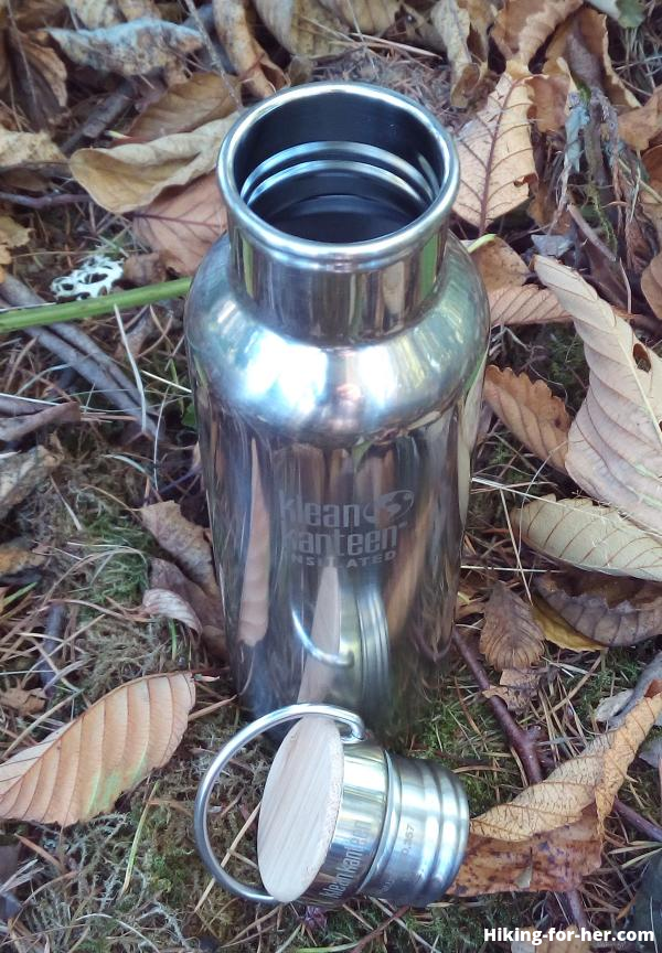 Klean Kanteen metal water bottle and metal cap with bamboo insert, resting on autumn leaves