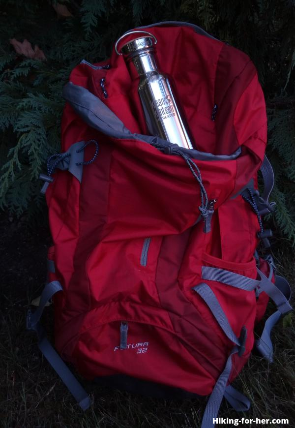Shiny metal water bottle sitting on bright red hiker's backpack in low light conditions at dusk