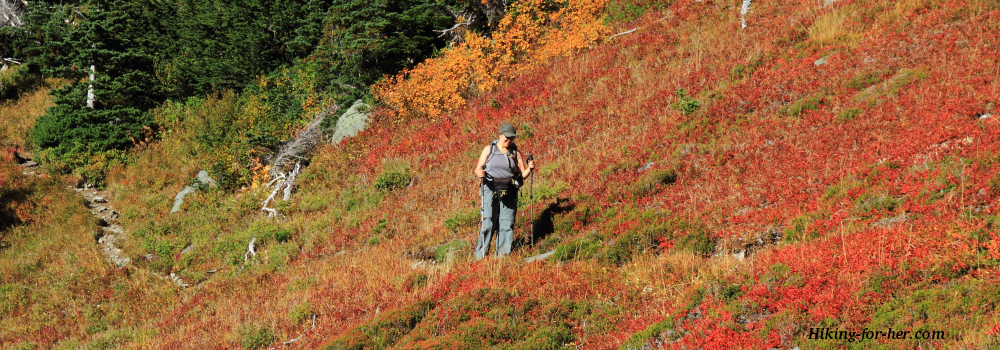 Female hiker on a trail through autumnn foliage
