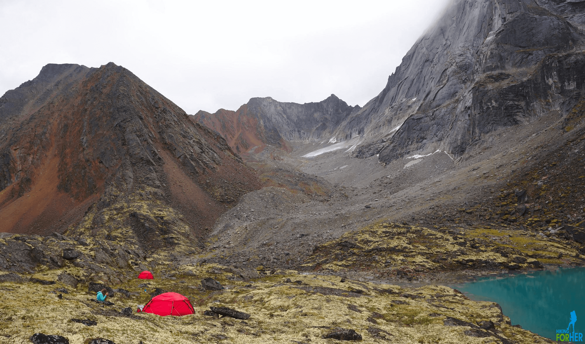 Backcountry wilderness camp with 2 red tents and a brilliant blue lake surrounded by dark towering mountains