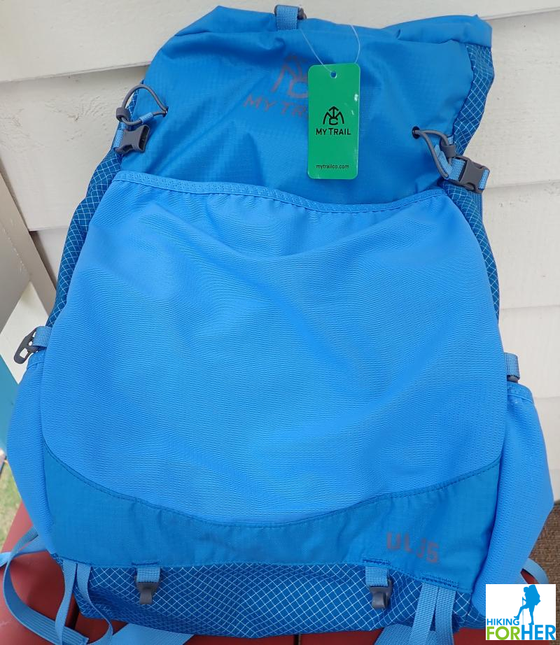 My Trail Co women's hiking day pack in blue, with green company tag attached