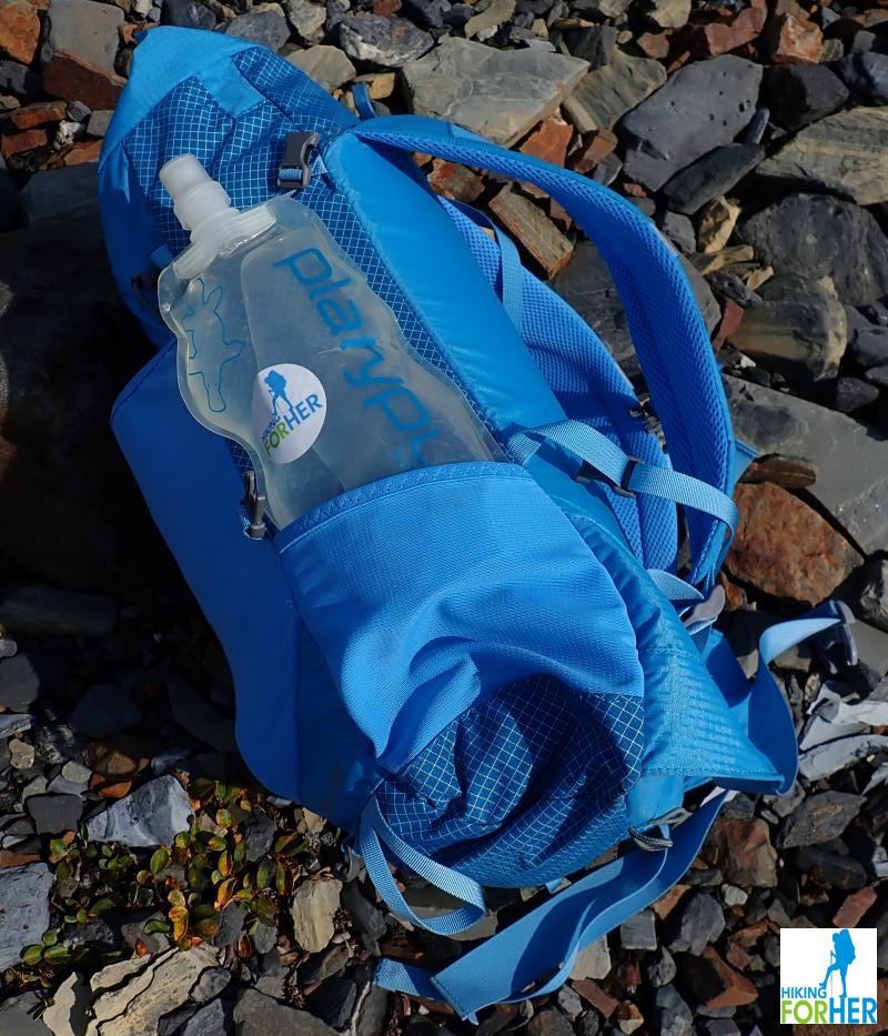 Blue day pack laying on its side on rocks, holding a water bottle with a Hiking For Her sticker