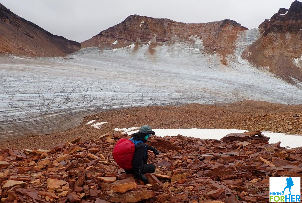 Female hiker wearing a backpack with a red rain cover, sitting on talus pile, viewing an unnamed glacier in the Ragged Range, NW Territories