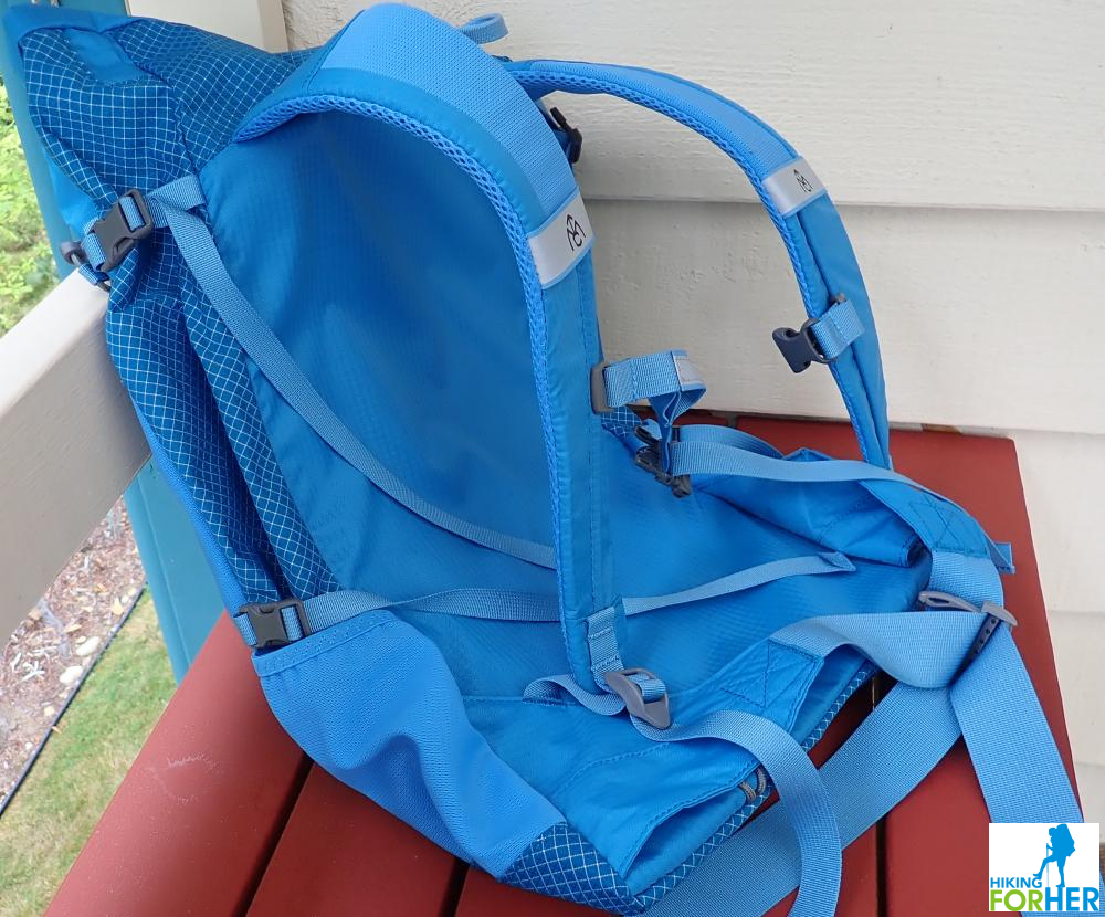Women's blue hiking day pack lying empty, showing mesh side pocket, straps and buckles