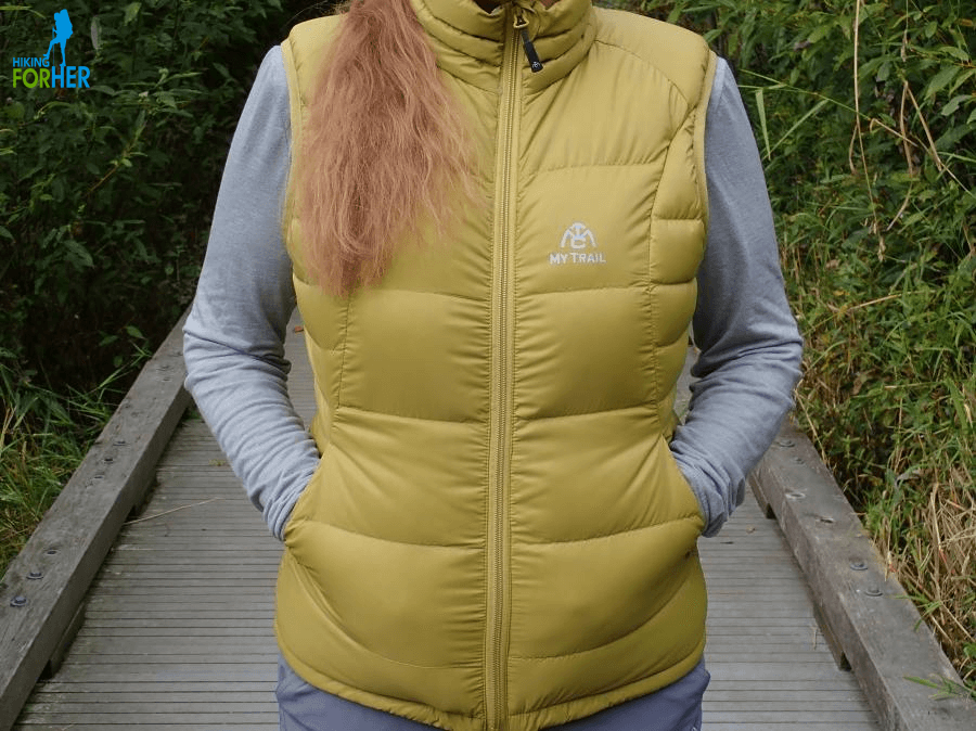 Female hiker wearing a yellowish green down hiking vest, with hands in pockets