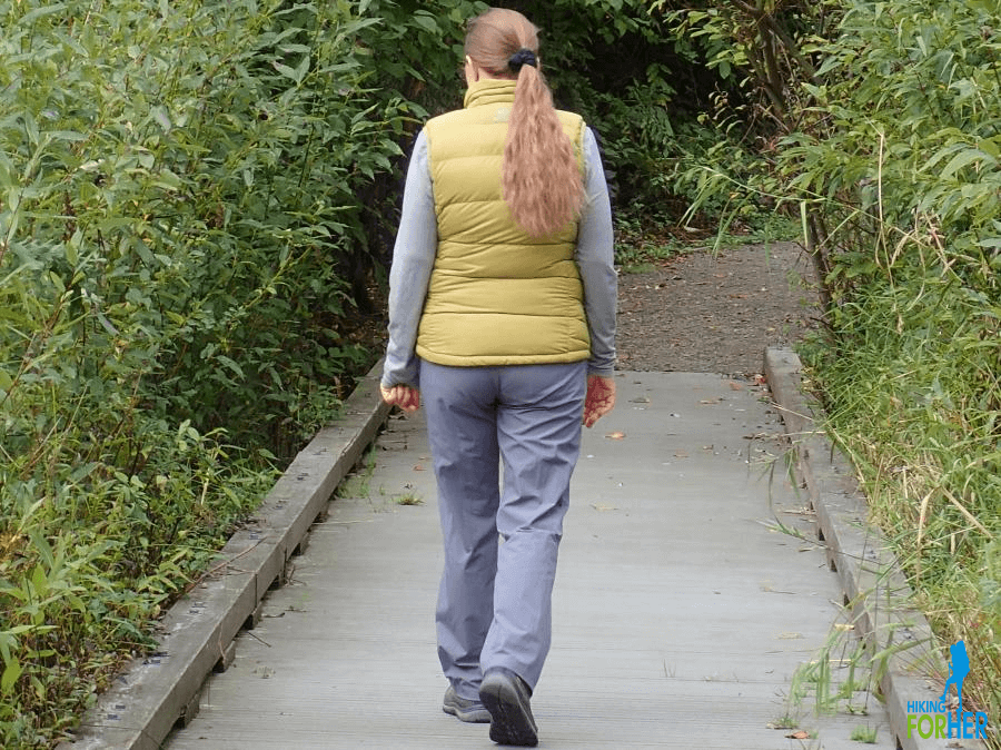 Female hiker walking over bridge wearing yellow down vest and gray hiking pants